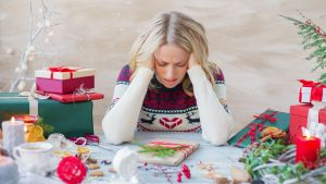 Image of a woman at a table surrounded by Christmas gifts. This image depicts the stress that comes up during the holidays, which can be decreased by using anxiety treatment in Castle Rock, CO. | 80109