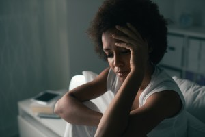 A photo of a Black woman sitting in bed and looking stressed. She is thinking about a traumatic memory that is causing her to experience symptoms of PTSD. She is going to reach out to a trauma therapist for PTSD treatment in Castle Rock, CO. 80104 | 80109 | 80108