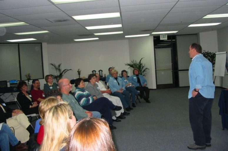 A person gives a presentation standing before an audience that sits in chairs.