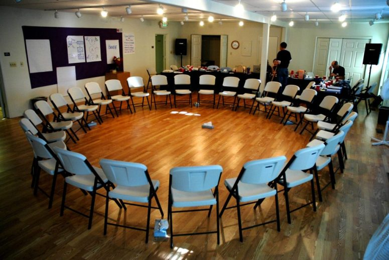 A large circle of empty chairs in a room with tables and a couple people in the back.