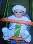 Baby Laura in swing with smart fur hat
