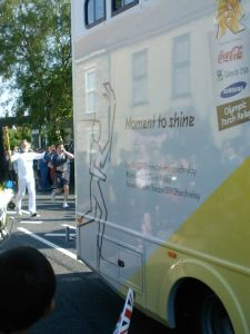 Official Olympic bus followed by torchbearer