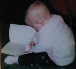 Baby Laura reading a grown-up book, aged less than 1