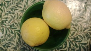 Two lemons in a green bowl