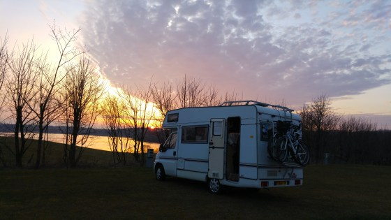 Camper van against sunset with lake