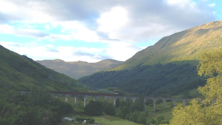 Train on multi-arched viaduct with scenic highland mountains behind