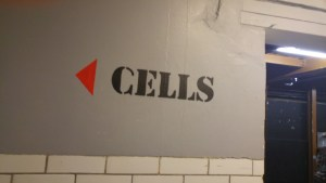 """image of """"Cells"""" stencilled in black on to a grey wall"""