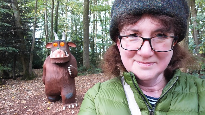 photo of Debbie Young in Harris Tweed hat with large sculpture of Gruffalo behind her