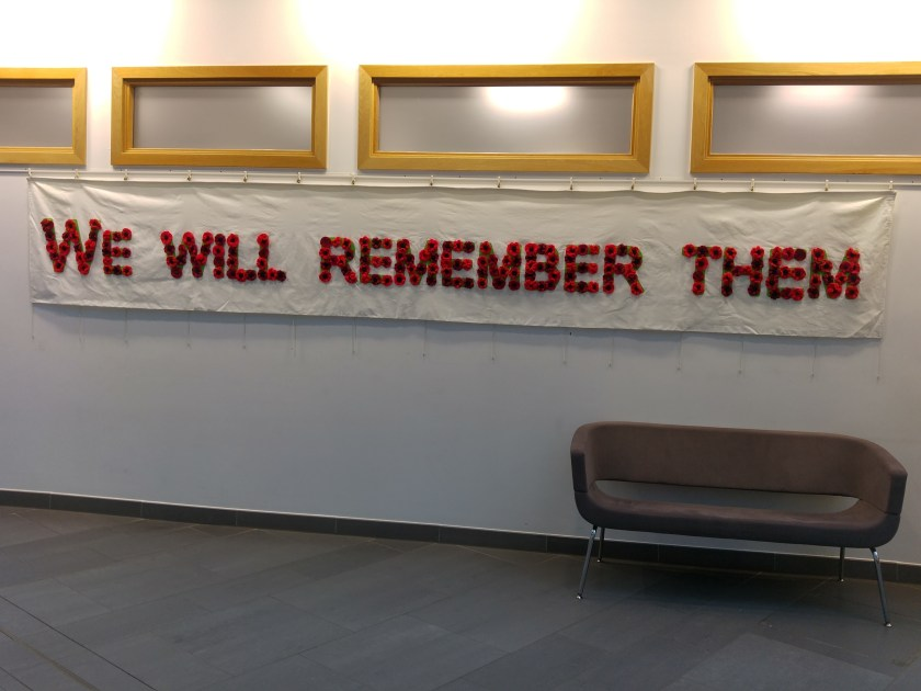 "banner on wall with ""we will remember them"" spelled out in knitted poppies"