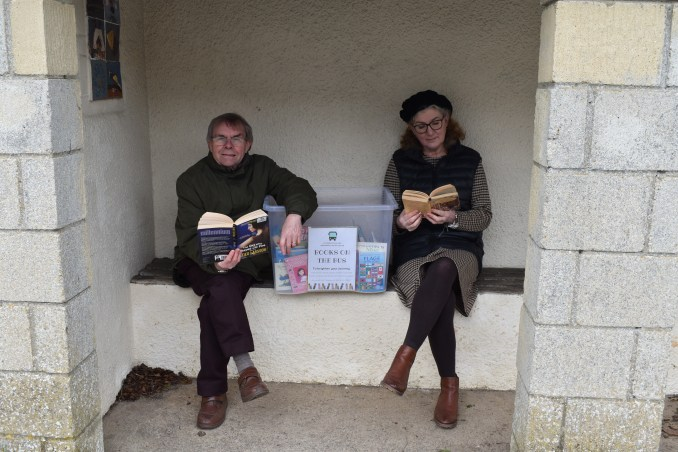 Photo of parish councillor and Debbie reading books in bus stopJohn