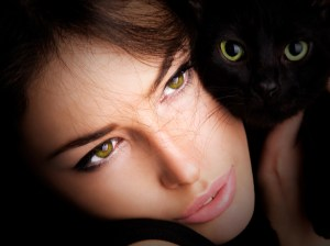 beautiful young woman portrait with black cat, close up