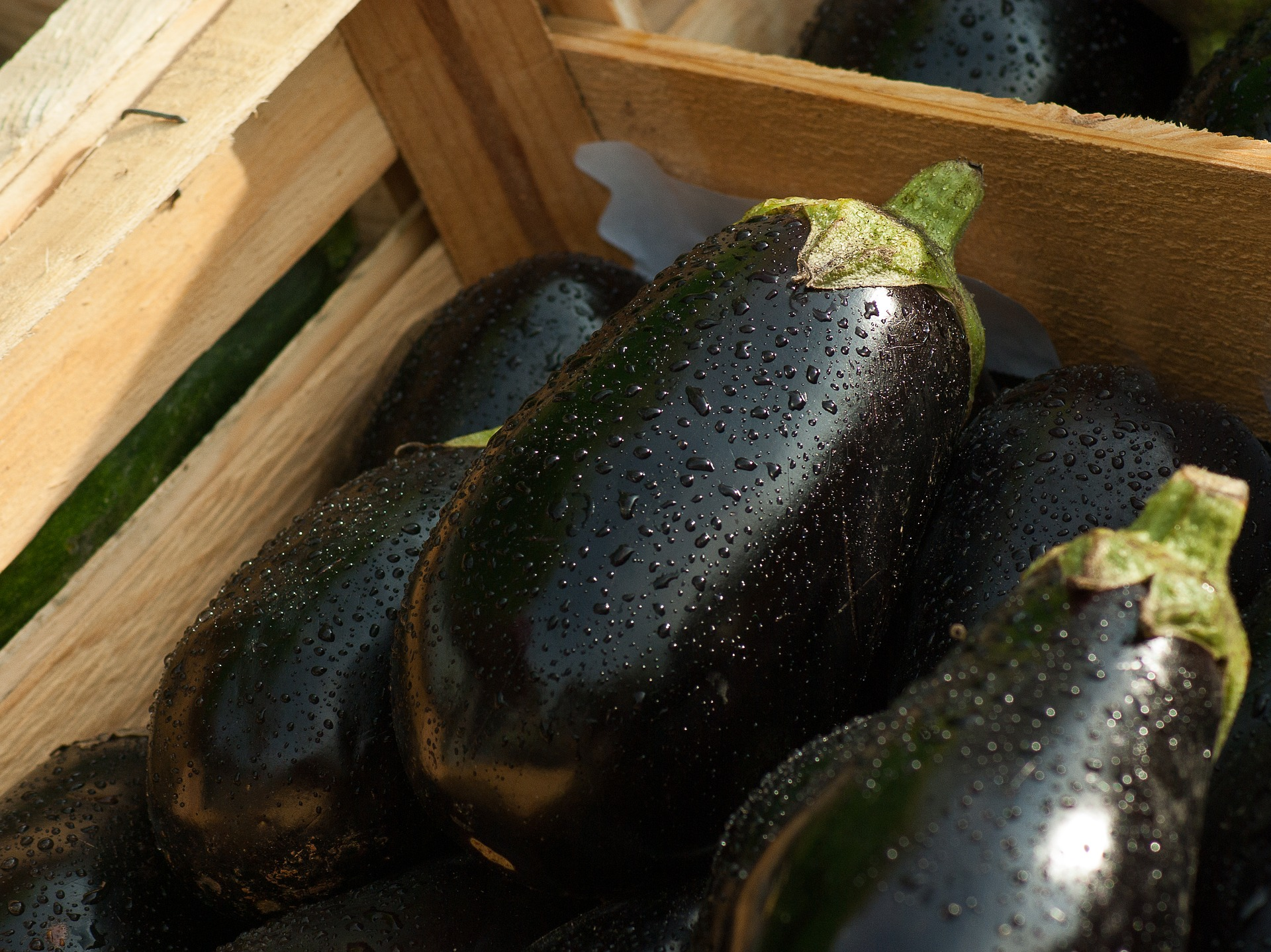 Image by Jacqueline Macou from Pixabay, wet eggplant stacked in a wooden crate at market