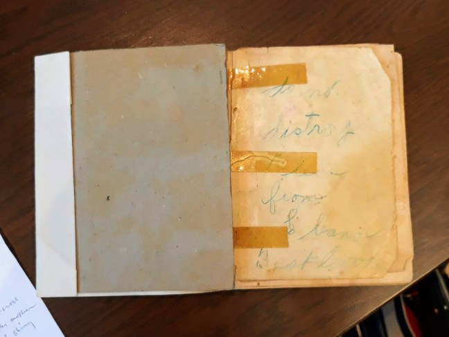 inside of old tattered book with tape and faded handwriting