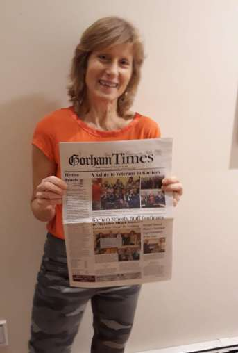 author s.m. stevens posing with gorham times newspaper