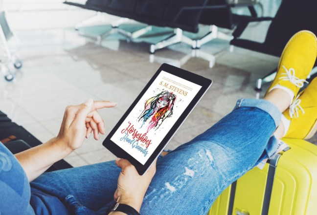 novel on table in lap of woman wearing jeans and yellow sneakers in airport