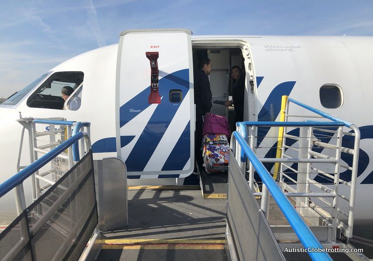 Alaska Airlines Exceeds Expectations Despite a 2 Hour Delay crew helps with carry on