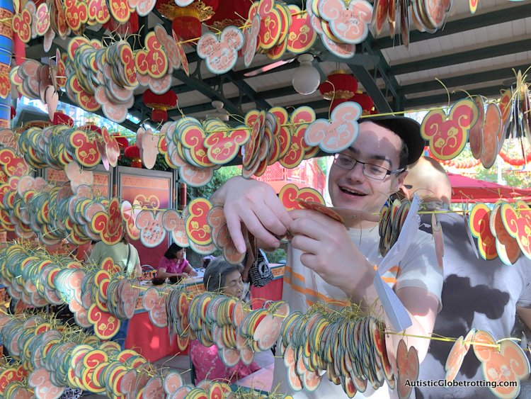 Attending Disneyland's Lunar Year Celebrations with Autism tying his paper wish on the wall