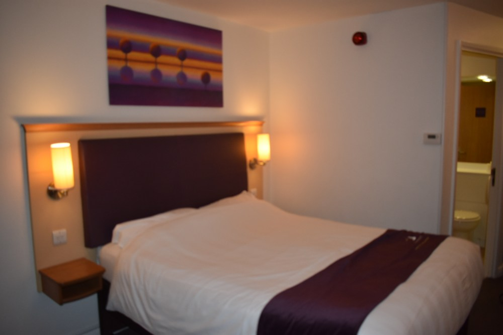 A comfy looking double bed with a light either side and a picture on the wall behind.