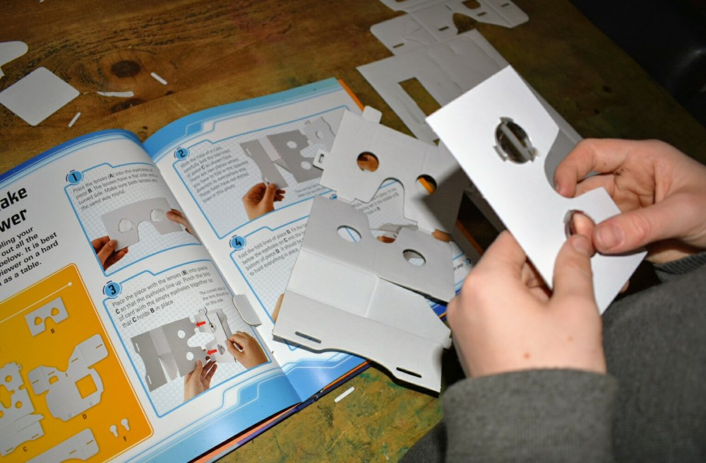 A childs hands making a Virtual Reality viewer and following instructions from the book.