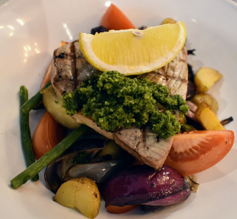 A plate of roasted vegetables and potatoes. There is a tuna steak on top with green pesto and a slice of lemon.