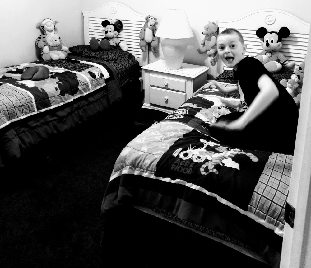 A black and white photo of a boy sat on his bed smiling
