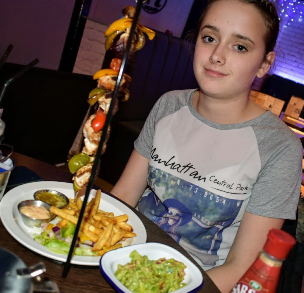 A girl with a hanging kebab of chicken, vegetables and lime. On the plate is a pile of fries and some salad