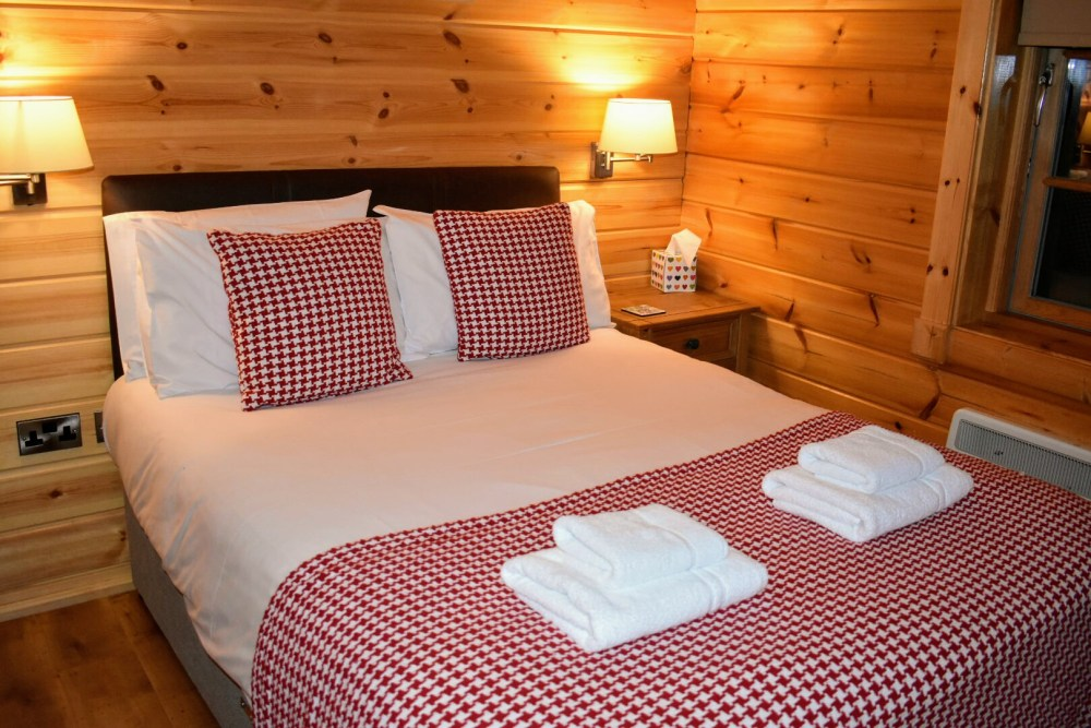 A double bed with white sheets and a red and white checkered bed spread