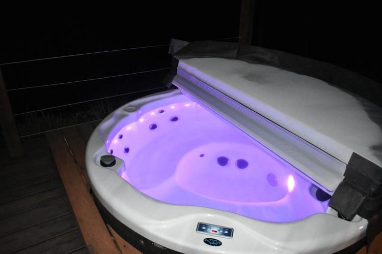 A hot tub at night, lit purple