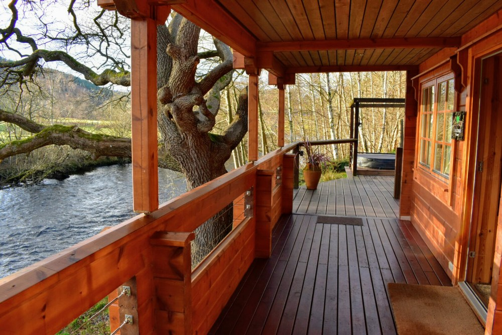A decked outside area with a hot tub at the end