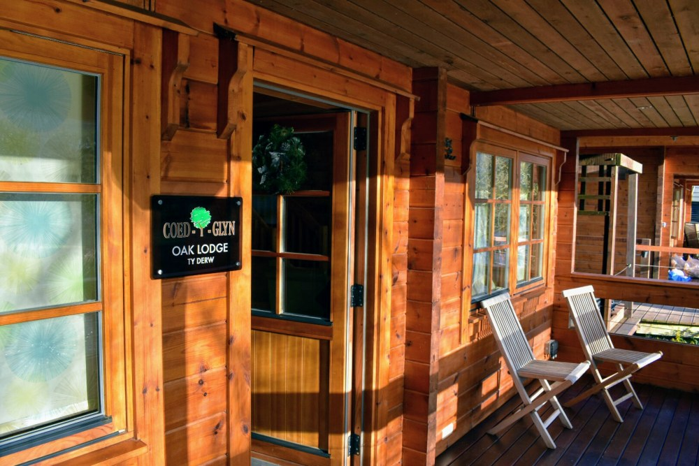 The outside of Oak Lodge at Coed-y-glyn Log Cabins. There are two chairs outside.