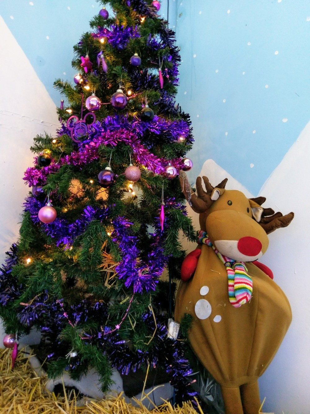 A Christmas tree, decorated in mostly purple decorations. Next to the tree is a model reindeer.