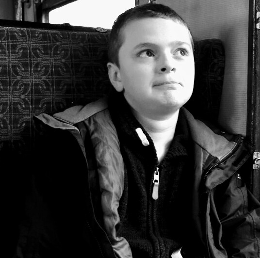 A black and white picture of a boy looking confused