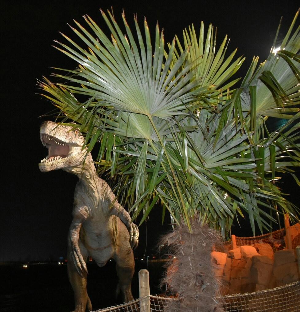 A large dinosaur next to a palm tree