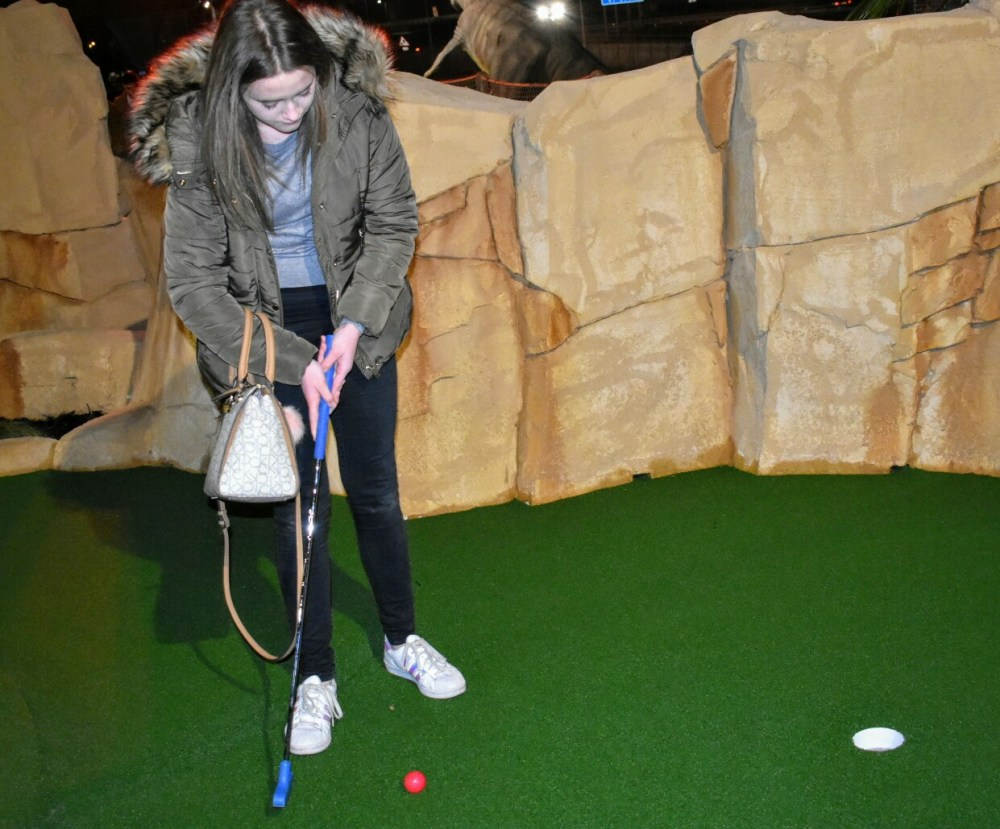 A girl playing golf.