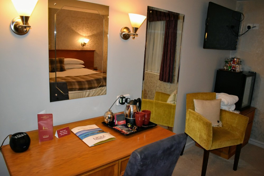 A hotel room with desk and chair