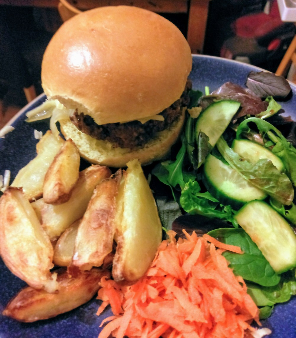 A homemade burger in a brioche bun with wedges and salad