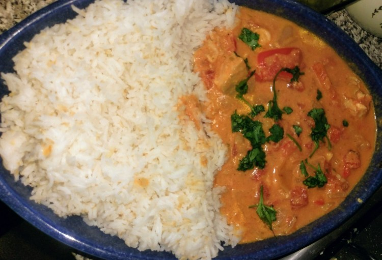 A bowl with rice on one side and fish curry on the other