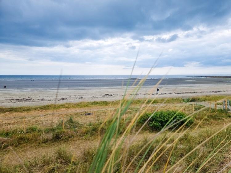 Tyrella beach in Northern Ireland with vast sand, sand dunes and sea.