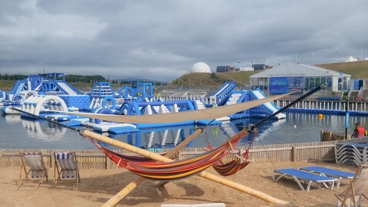 A hammock on the beach. Behind it is Lets go Hydro inflatable water park in Northern Ireland. Giant inflatables on the lake to play on.