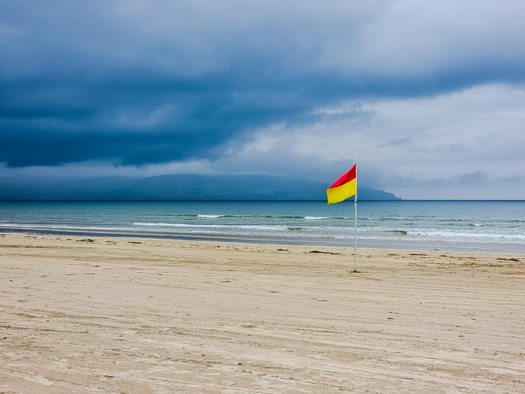 A red and yellow flag at Downhill beach northern ireland