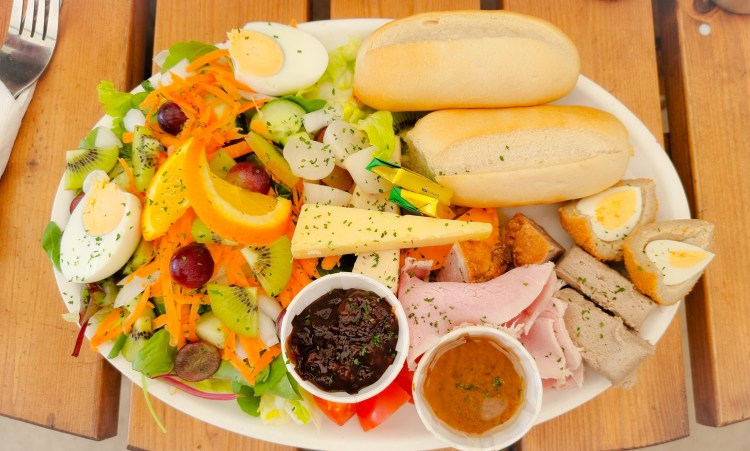 Ploughmans platter with salad, fruit, egg, scotch egg, pork pie, chutneys, bread, cheeses and ham at the Hanging Gate pub in chapel-en-le-firth