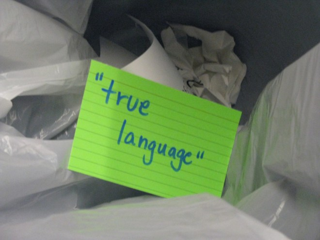 A notecard bearing the words TRUE LANGUAGE sits in a recycling bin
