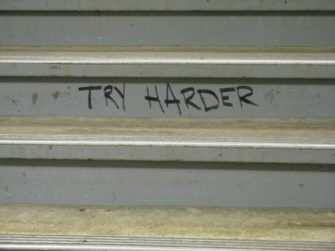 The words TRY HARDER painted on a stair