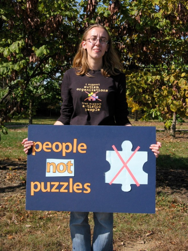 Me, a white woman with blonde hair, holding a blue sign that reads People not puzzles. There is also a light blue puzzle piece crossed out in red on the poster.