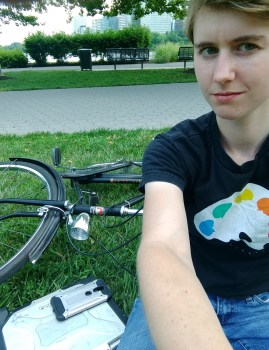 Me with my bike, laptop, and phone on some grass