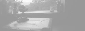 This image is a background behind text, a faded image of my laptop sitting with bottles and an old telegraph machine in a window. A mountain view is in the background.