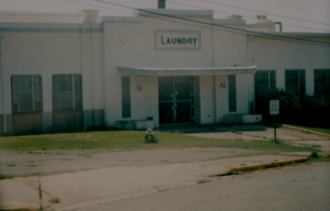 a large, rundown, white building with the word 'laundry' on the sign above the door looks abandoned and desolate