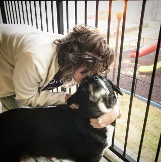 Jess giving her dog Abby a kiss on her head. Abby is a border collie mix.