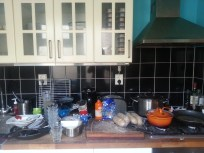 View of the kitchen counter - there are more dirty dishes and cups stacked on the floor