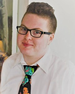 Cori, a nonbinary person wearing glasses, smiles at the camera